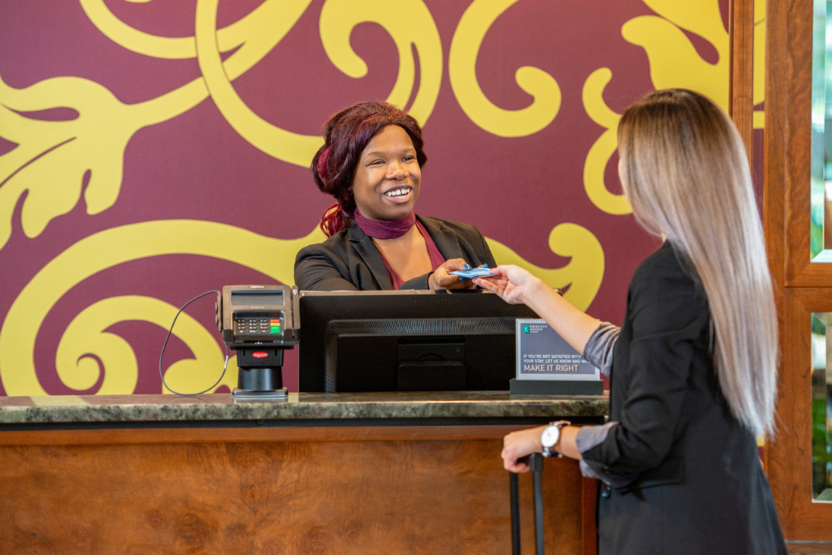 An Embassy Suites Buffalo Employee Welcoming a Guest